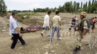 A la frontière avec l'Ouzbékistan, des réfugiés de la minorité ouzbèke rentrent au Kirghizistan, le 22 juin 2010.