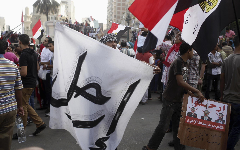 """""""Cút đi"""" là chữ viết tiếng Ả rập trên các biểu ngữ làm bằng vải trắng (REUTERS /Asmaa Waguih)"""