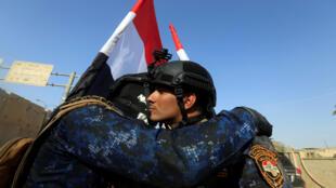 Dos combatientes de las fuerzas armadas tras anunciar la victoria en Mosul, 9 de julio de 2017.