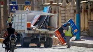 Des employés municipaux retirent les affiches électorales des rues, dans le centre de Najaf, le 13 mai, au lendemain des législatives en Irak.