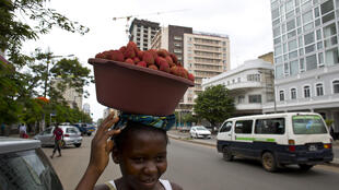 A street vendor carries lychees in Maputo