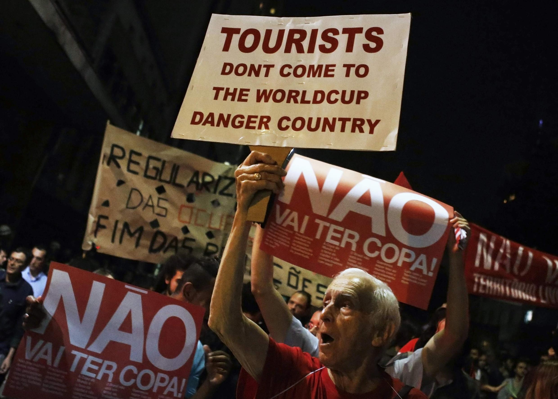 Демонстранты против проведения ЧМ по футболу с лозунгами, призывающими туристов не приезжать на чемпионат.Сао Пауло 15/05/2014 (архив)