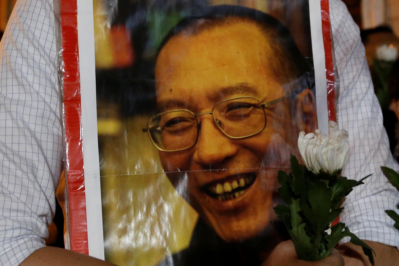 香港民主人士7月13日在中联办门前捧着刘晓波的照片寄托哀思