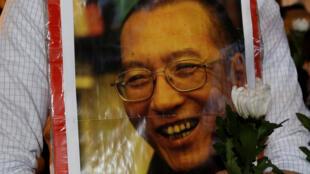 香港民主人士7月13日在中聯辦門前舉着劉曉波的照片寄託哀思