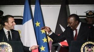 Rais wa Ufaransa Emmanuel Macron (kushoto) akipeana mikono na Rais wa Kenya Uhuru Kenyatta wakati wa hafla katika Kituo Kikuu cha Reli cha Nairobi jijini Nairobi, Machi 13, 2019, siku ya kwanza ya ziara ya kiserikali nchini Kenya.