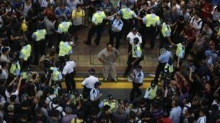A polícia cerca um homem ferido no bairro de Mong Kok, neste sábado (4), em Hong Kong.