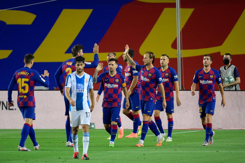 Os jogadores do FC Barcelona festejam o triunfo por 1-0 perante o desalento do futebolista do Espanyol.