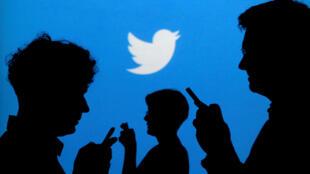 La silueta de personas sosteniendo un teléfono móvil con el logo de Twitter detrás.