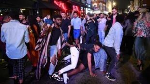 Le 4 juillet 2020, les fêtards dansent dans la rue dans le quartier de Soho à Londres, à la suite d'un nouvel assouplissement des restrictions visant à autoriser l'ouverture des pubs et des restaurants pendant la pandémie du nouveau coronavirus Covid-19.