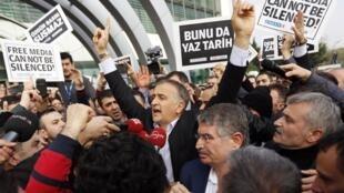 Le rédacteur en chef de «Zaman», Ekrem Dumanli, entouré de ses collègues et de policiers en civil, quittant les locaux du journal, à Istanbul, le 14 décembre 2014.