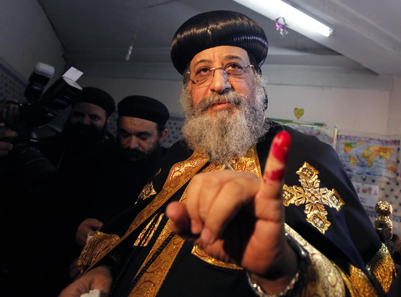 Le patriarche copte Tawadros II, montrant son doigt taché d'encre, dans un bureau de vote du Caire, le 14 janvier 2014.