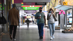 La gente camina por una avenida generalmente concurrida en el distrito central de negocios en Melbourne, Australia, el 28 de mayo de 2021