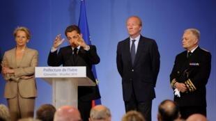 Nicolas Sarkozy entre Michèle Alliot-Marie (G) et Brice Hortefeux (D) pendant son discours à Grenoble.