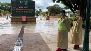 À Hong Kong, des employés de Disneyland portant un masque après que le parc d'attraction a été fermé, le 26 janvier 2020.