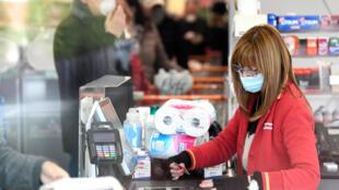 Una trabajadora lleva una máscara en un supermercado de la ciudad de Casalpusterlengo, que ha sido puesta en cuarentena por el gobierno italiano debido a un brote de coronavirus en el norte de Italia, el 23 de febrero de 2020. REUTERS/Flavio Lo Scalzo