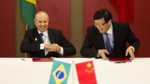 O ministro da fazenda, Guido Mantega (à esq.) e o ministro chinês de Finanças, Lou Jiwei, durante o ato de assinatura do acordo em Durban.