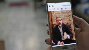 Une personne regarde la vidéo Facebook de Rami Makhlouf dans laquelle l'homme d'affaires se plaint publiquement du régime syrien, le 11 mai dernier à Damas.