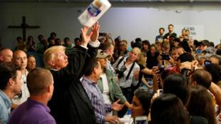 El presidente estadounidense Donald Trump arrojando un rollo de papel absorbente a damnificados por el huracán María. San Juan, Puerto Rico, el 3 de octubre de 2017.