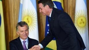 Presidentes argentino e brasileiro cumprimentam-se em Brasilia para assinatura de um acordo a 16 de Janeiro de 2019.