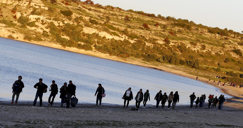 Des réfugiés longent une plage turque, dans la province d'Izmir, avant de se diriger vers l'île grecque de Chios.