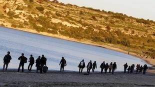 Des réfugiés longent une plage turque, dans la province d'Izmir.
