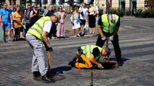 Nhân viên an ninh Phần Lan niêm phong miệng cống trước cửa tòa đô chính Helsinki. Ảnh ngày 13/08/2018.