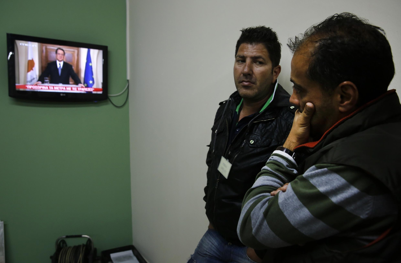 Des chypriotes regardent l'intervention du président Nicos Anastasiades à la télévision, le 25 mars 2013