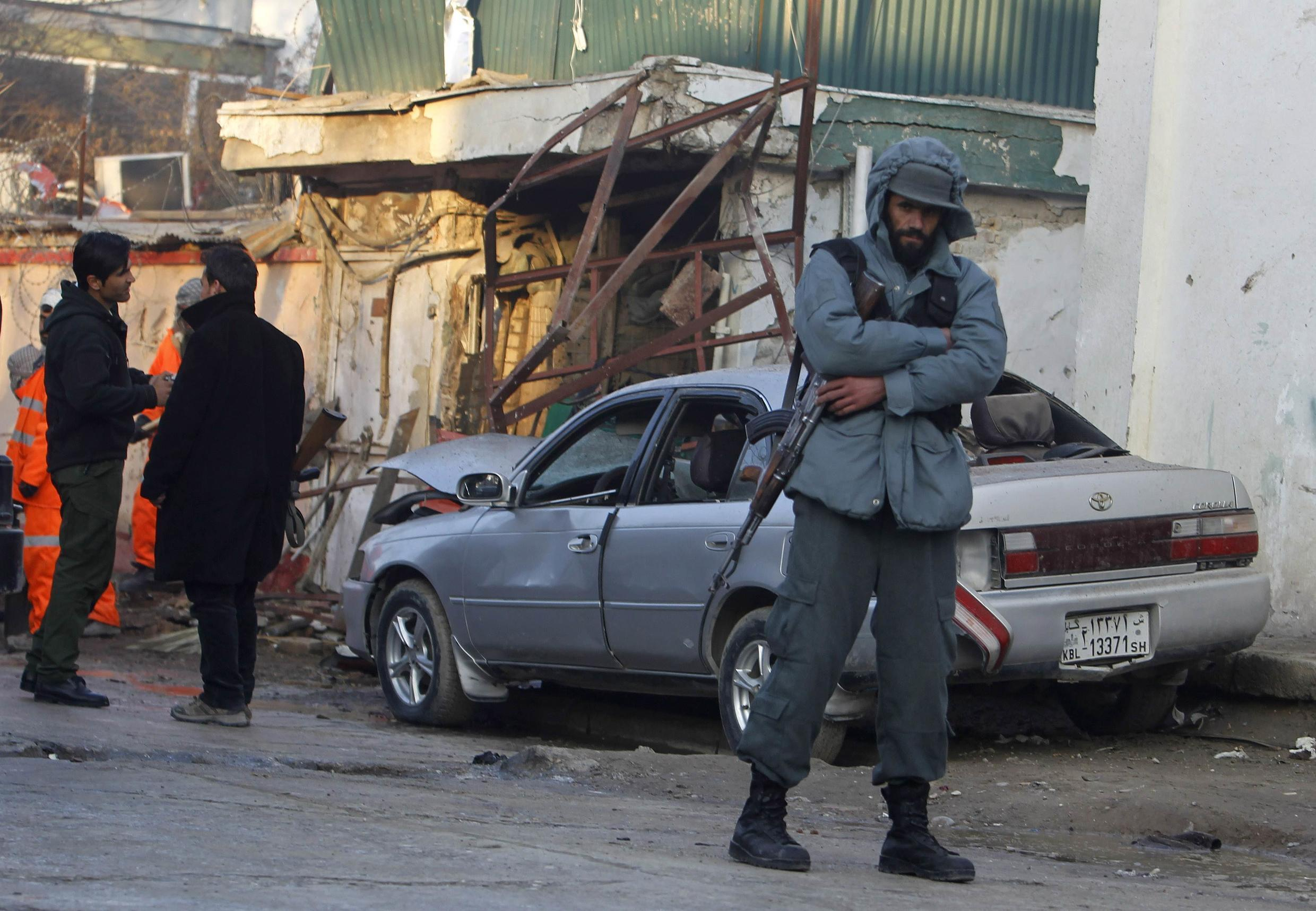 An Afghan policeman stands near a damaged car after a suicide attack in Kabul, 18 January, 2014