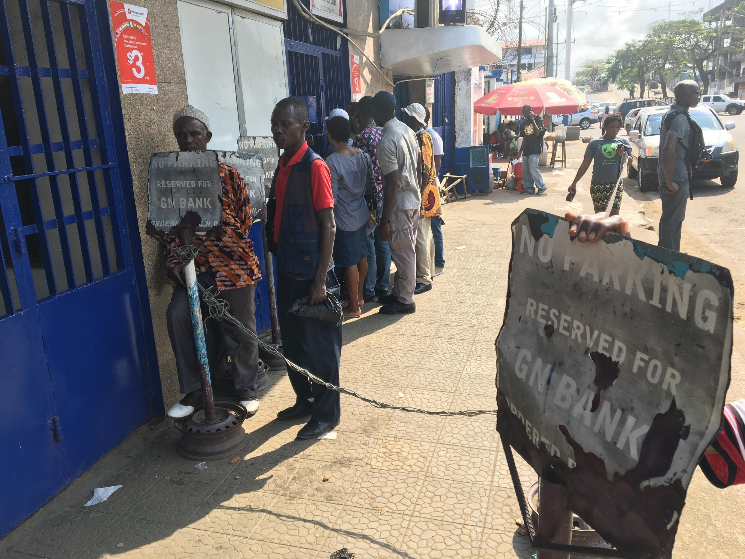 People queue outside SIB Liberia bank in Monrovia, waiting to try and withdraw cash. SIB was recently renamed, it was formerly known as GN Bank.