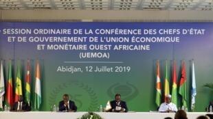 Le président ivoirien, Alassane Ouattara, et le président de la Commission de l'UEMOA, Abdallah Boureima (d), lors du sommet des chefs de l'État, à Abidjan, en Côte d'Ivoire, le 12 juillet 2019.