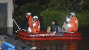 Des habitants évacués par les secours de leur maison inondée avec le passage du typhon Talim, dans le sud du Japon, le 17 septembre 2017.
