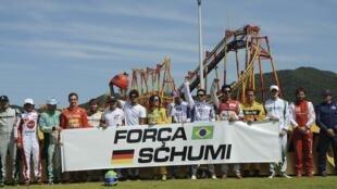 """Liderados por Felipe Massa,(6°à esq.) pilotos prestam homenagem a Schumacher, e estenderam uma faixa com a mensagem """"Força Schumi""""."""