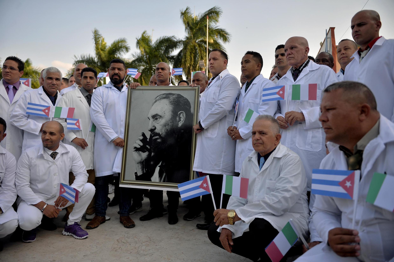 Des médecins cubains posent devant le portrait de Fidel Castro avant leur départ pour l'Italie, le 21 mars 2020.