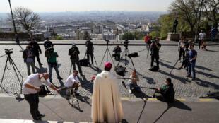 Des journalistes respectent la distanciation sociale alors qu'ils interviewent l'archevêque de Paris, Michel Aupetit, devant la basilique du Sacré-Cœur de Montmartre, le 9 avril 2020.