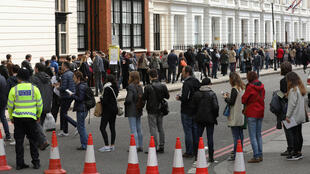 French expats queue along the street outside the Lycee Francais Charles de Gaulle to cast their vote in a polling station inside the school, in the first round of the 2017 French presidential election, in London, Britain April 23, 2017.