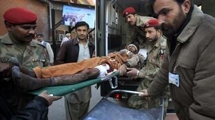 Paramedics and soldiers assist a man who was injured during a suicide bomb attack in Bajaur region