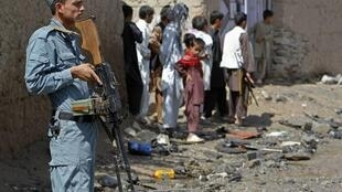 An Afghan policeman keeps watch at the site where a remote-controlled bomb hit a bus, in the Paghman district of Kabul