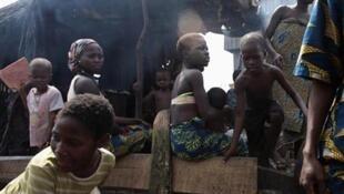 Wasu mazauna yankin Makoko, zaune a kofar gida, wadanda suka fi dogaro kan sana'ar kamun kifi, a birnin Legas dake Najeriya. (21/11/2009).