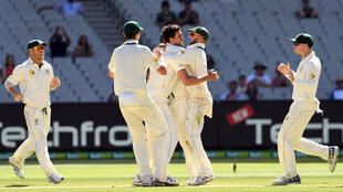 Australia's Mitchell Starc (C) is congratulated by teammates after dismissing Pakistan batsman Sarfraz Ahmed on the final day of the second cricket Test match in Melbourne on December 30, 2016.