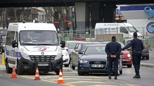 Police officers stop cars with even number licence plates in Paris on Monday