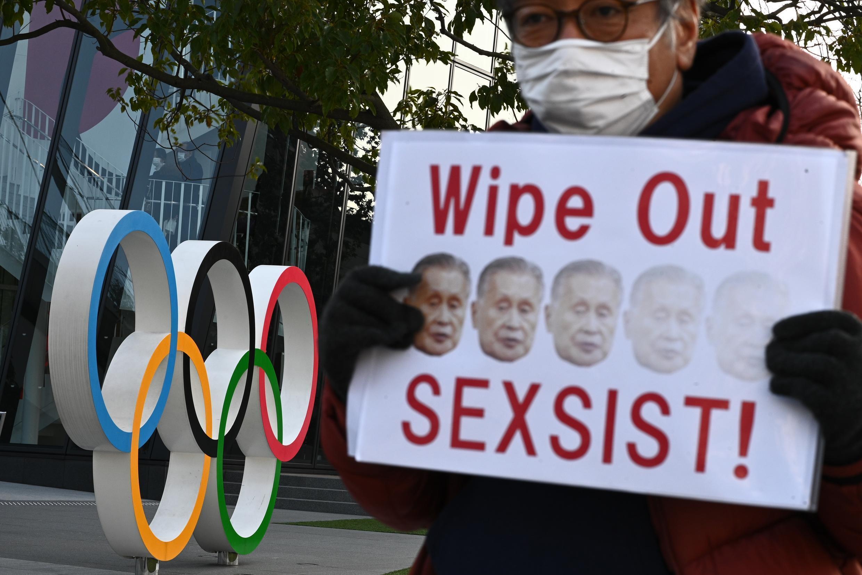 Un manifestant brandit une pancarte avec la légende «Éffacer le sexiste» et l'image de Yoshiro Mori devant le siège du Musée olympique de Tokyo, le 11 février 2021.