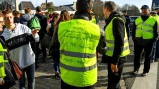 """Um manifestante dos coletes amarelos protesta contra o aumento das taxas.  Nas  suas costas podemos ler : """"Fora Macron!""""."""