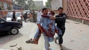 Men carry an injured man to a hospital after a car bomb in Jalalabad city, Afghanistan June 17, 2018. REUTERS