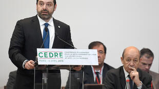 Lebanese Prime Minister Saad Hariri delivers a speech as French Foreign Minister Jean-Yves Le Drian (R) listens to during the Cedar (CEDRE) Conference for international donors and investors to support Lebanon's economy, in Paris, France, April 6, 2018.