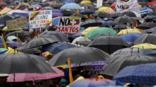 Forêt de parapluies sous la pluie dans la capitale colombienne : à Bogota, des dizaines de milliers de personnes ont marché contre les négociations engagées par le président Juan Manuel Santos avec les guérillas des Farc et de l'ELN, le 2 avril 2016.