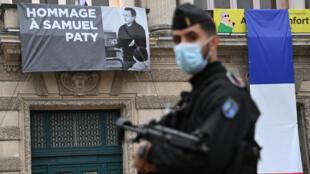 Un policía francés monta guardia frente a un teatro del que cuelga un cartel con una imagen de Samuel Paty durante un homenaje nacional al profesor asesinado, el 21 de octubre de 2020 en la ciudad de Montpellier, al sureste de Francia