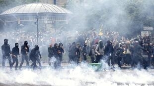 Le gaz lacrymogène sont tirés lors d'affrontements avec des gendarmes français lors d'une manifestation pour protester contre les réformes du Code du travail, à Paris le 26 mai 2016.