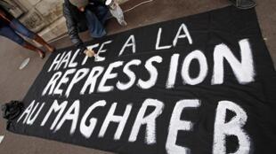 """Manifestações na Tunísia e Marrocos devido a insatisfação quanto ao desemprego e a uma grave crise social. Cartaz com dizeres: """"A baixo a repressão no Magreb""""."""