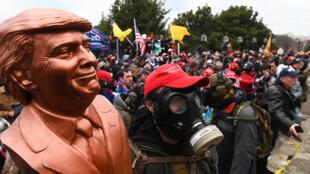 Un partidario del presidente de  Estados Unidos, Donald Trump, usa una máscara de gas y sostiene un busto del mandatario después de que él y cientos de personas irrumpieron en el Capitolio