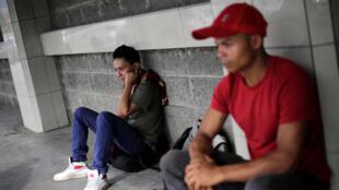Dos jóvenes esperan en la terminal de buses de San Pedro Sula, para partir con la caravana hacia los Estados Unidos.